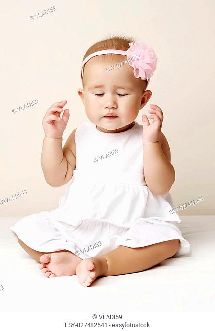Beautiful little cute baby girl in a white dress and with flower smiling