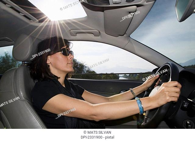 A woman driving a car with sunlight shining in the sunroof;Locarno ticino switzerland