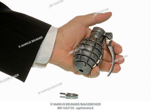Business man holding a hand grenade, danger