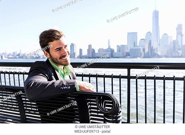 USA, smiling man sitting on bench at New Jersey waterfront with view to Manhattan
