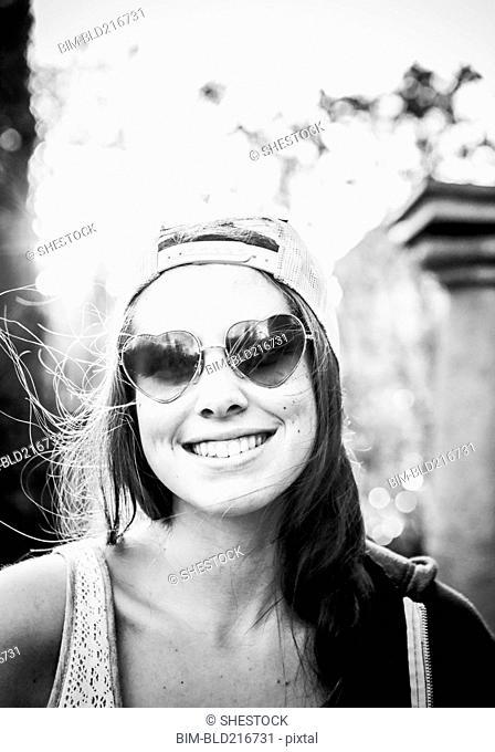 Caucasian teenage girl wearing heart-shaped sunglasses