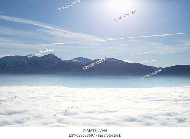 Sea of fog over an alpine lake with snow-capped mountain