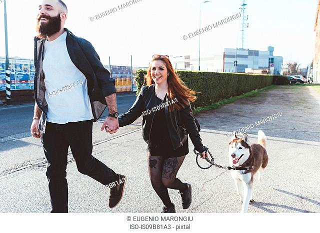 Couple walking with dog, Milan, Lombardia, Italy, Europe