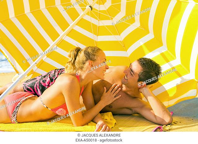 Two lovers enjoying their time on the beach under a sunshade