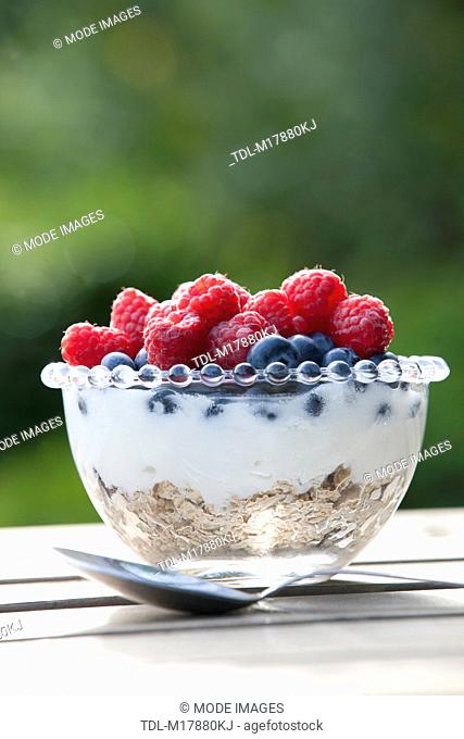 Granola, yoghurt, raspberries and blueberries in a glass dish with spoon