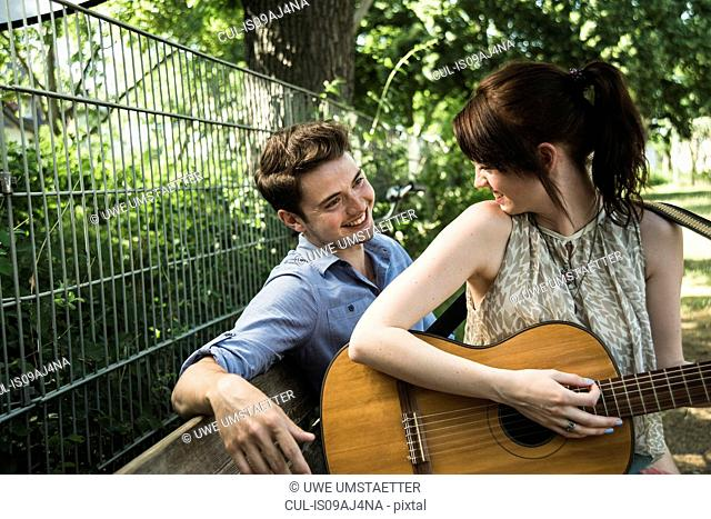 Young couple playing acoustic guitar in park