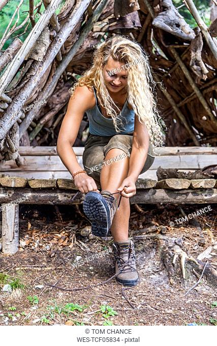 Young woman sitting on bench lacing her hiking boots