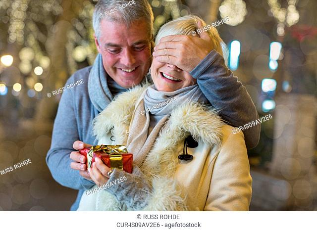 Mature man handing with xmas gift to wife on tree lined avenue, Majorca, Spain