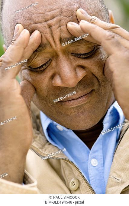 Grimacing mixed race man rubbing forehead
