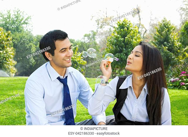 Businessman and businesswoman romancing in a park