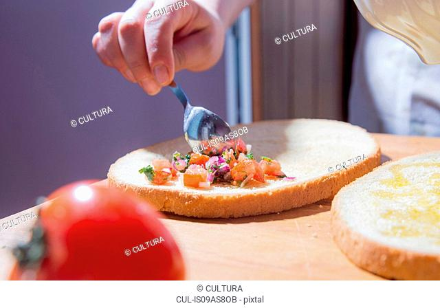 Hands of woman spreading ingredients on bread at kitchen counter