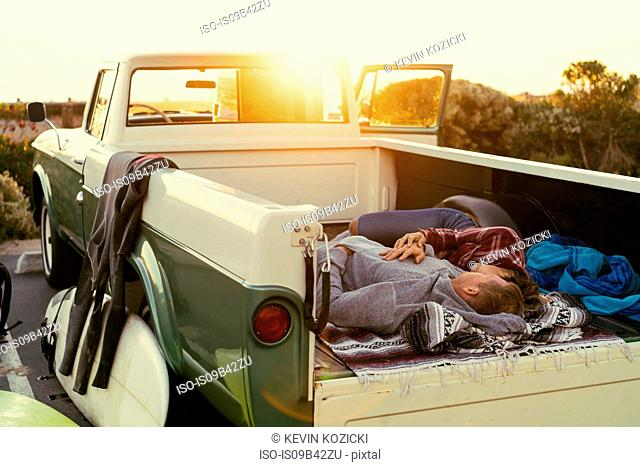 Surfing couple lying in back of pickup truck at Newport Beach, California, USA