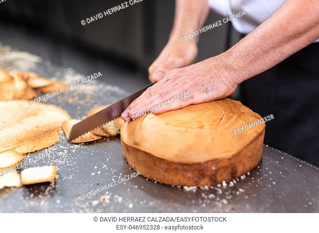 pastry chef cutting the sponge cake on layers. Cake production process