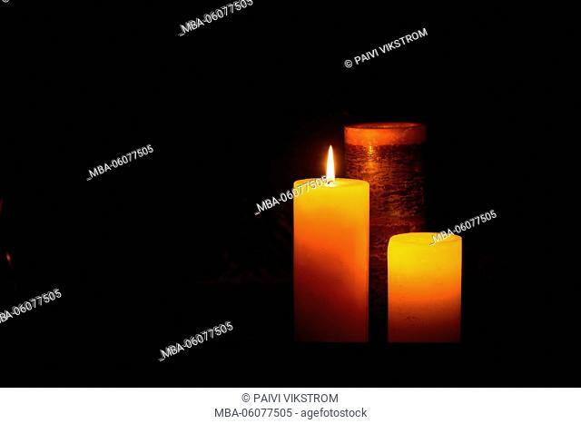 Three lit candles with dark blackground