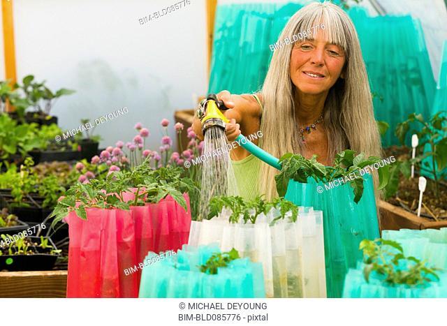 Caucasian woman watering plants in garden