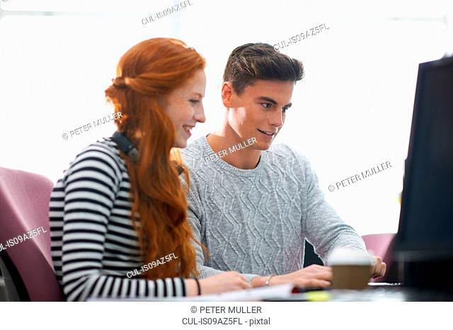 Young male and female college students at computer desk looking at computer