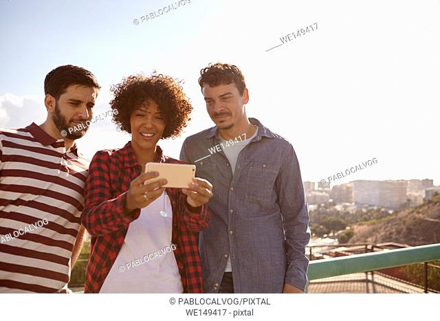 Three young millennials looking at cellphone the girl with the toothy smile between the guys is holding up for them all to see