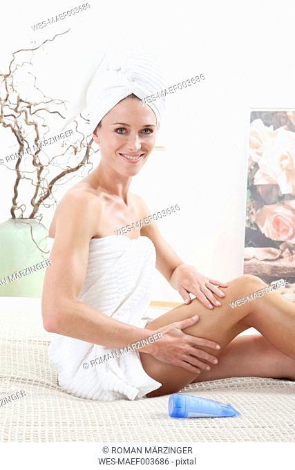 Young woman wrapped in towel applying body cream