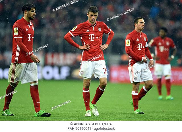 Munich's Javier Martinez (l-r), Thomas Mueller and Philipp Lahm leave the field after the DFB cup soccer match between Bayern Munich and Borussia Dortmund in...