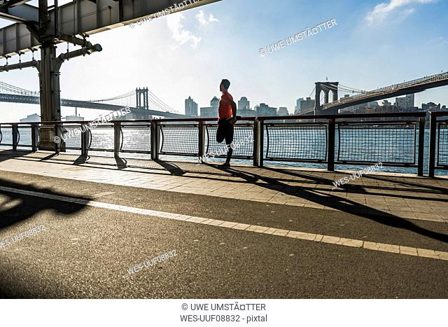 USA, New York City, sportive man stretching at East River