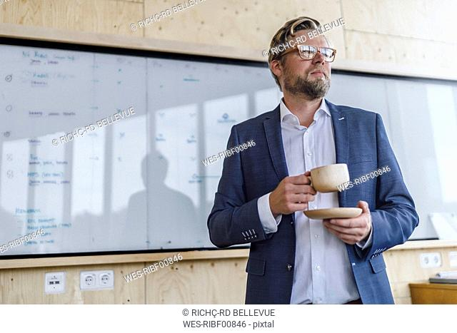 Businessman standing in his office in front of whiteboard, drinking coffee from a wooden cup