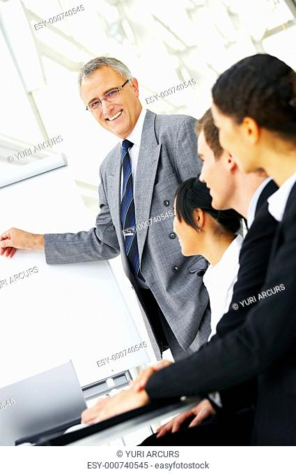 Mature Businessman Presenting On Office Whiteboard Stock