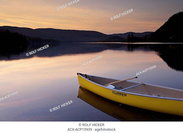 Canoe on the shore of Lac Monroe during sunset in Parc national du Mont Tremblant, a Provincial Park of Quebec, Laurentides, Quebec, Canada
