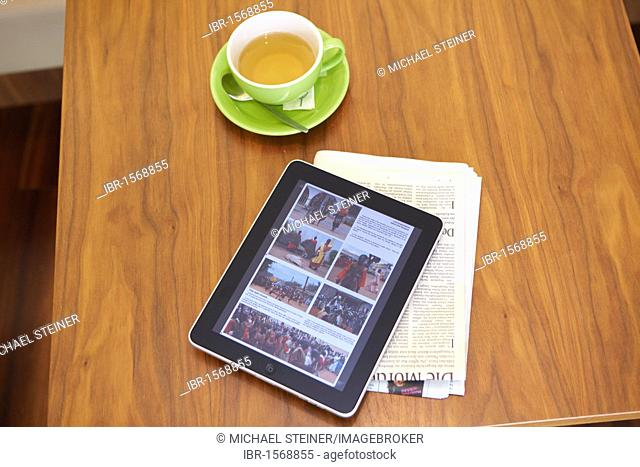IPad tablet computer with a teacup and a newspaper on a wooden table