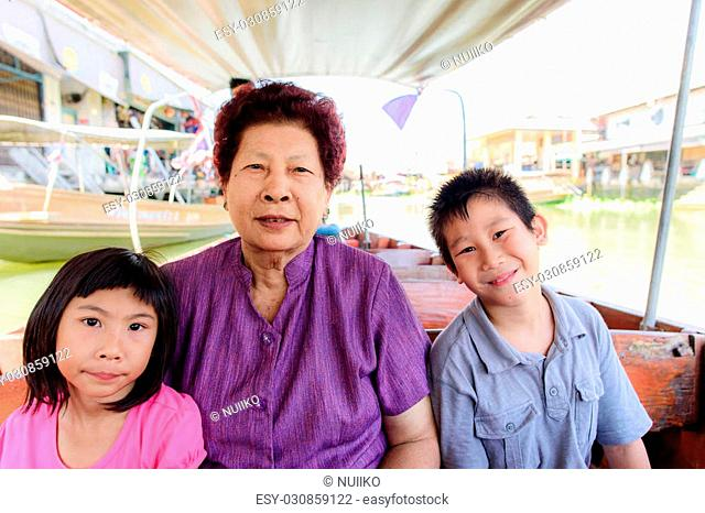 Happy Grandmother and children enjoying sightseeing long tail boat tour at floating market