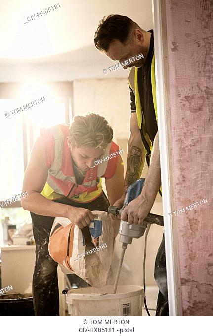 Construction workers mixing plaster