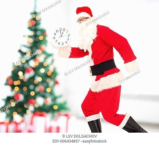 christmas, holidays and people concept - man in costume of santa claus running with clock showing twelve over living room and tree background