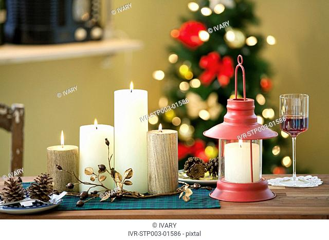 Christmas Candle And Lantern On Table In Front Of Decorative Christmas Tree