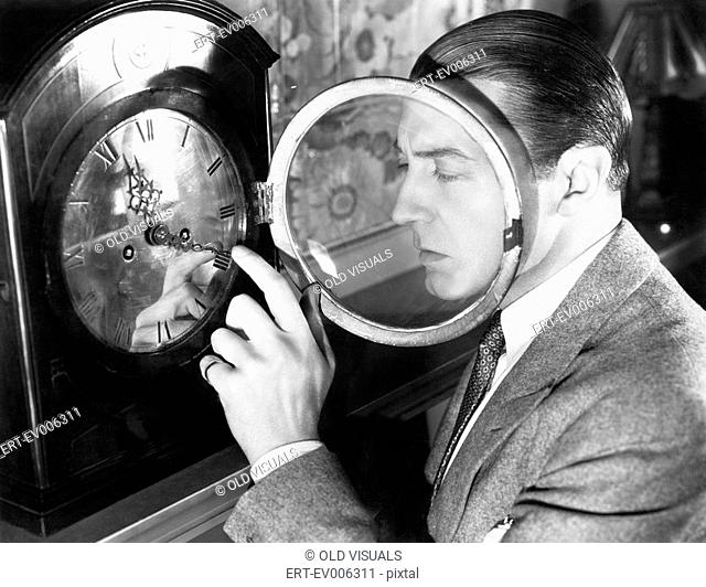 Man setting a clock All persons depicted are not longer living and no estate exists Supplier warranties that there will be no model release issues