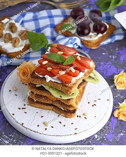 French toasts with strawberries and kiwi on a round white board, and top