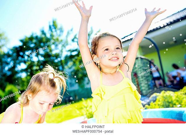 Children having fun in paddling pool in the garden
