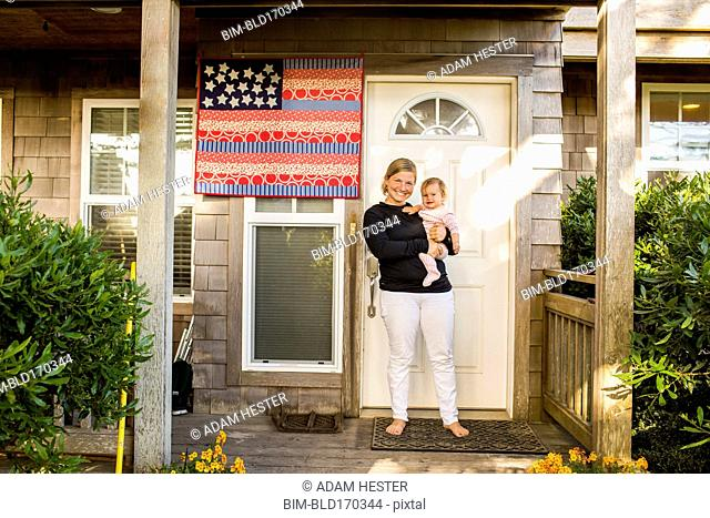 Caucasian mother holding baby daughter on front porch