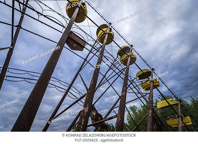 Yellow gondolas of ferris wheel in amusement park, Pripyat ghost city of Chernobyl Nuclear Power Plant Zone of Alienation in Ukraine