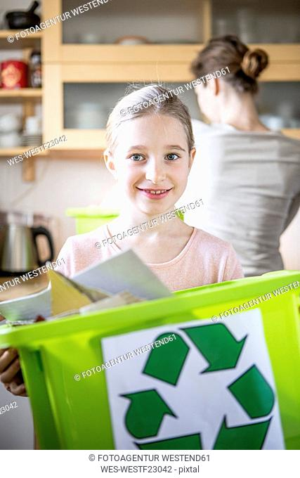 Portrait of smiling girl at home holding waste box