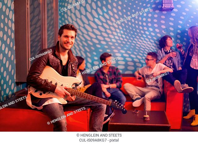 Mid adult man holding guitar sitting in front of group of teenagers