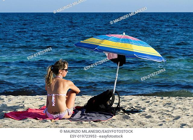 Girl sitting on the beach near the sunshade views sea blue