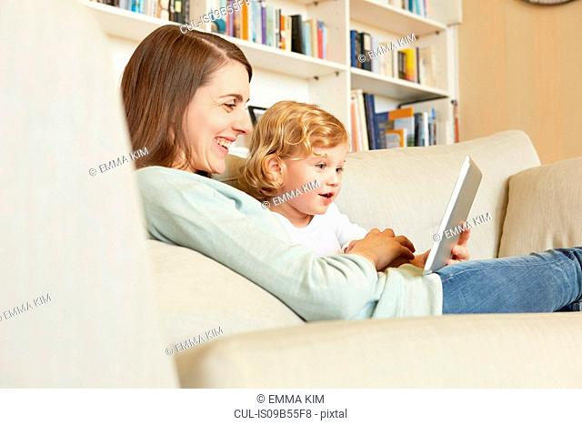 Female toddler sitting on sofa with mother looking at digital tablet