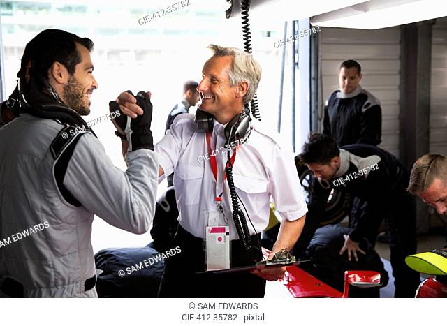 Manager and formula one driver celebrating, handshaking in repair garage