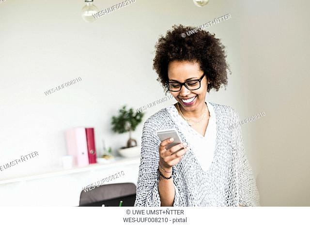 Smiling businesswoman in office looking at her smartphone