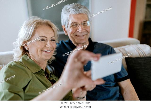 Senior couple at home sitting on couch taking a selfie
