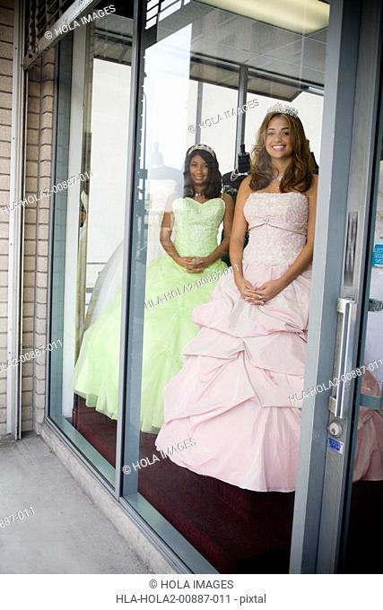 Girls posing as mannequins in dress shop window