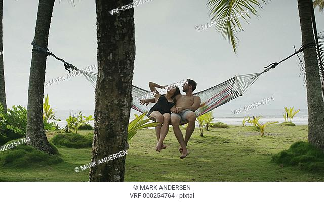 Slow motion panning wide shot of couple sitting in hammock / Esterillos, Puntarenas, Costa Rica