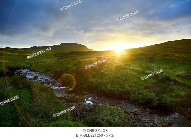 Sunrise over rural hills and stream