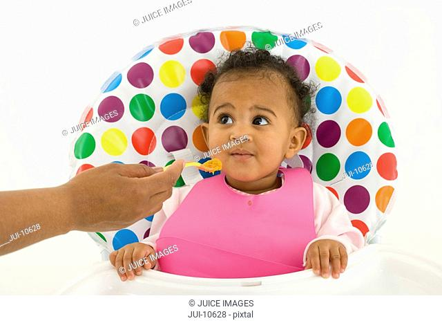Mother feeding baby girl 3-6 months in highchair
