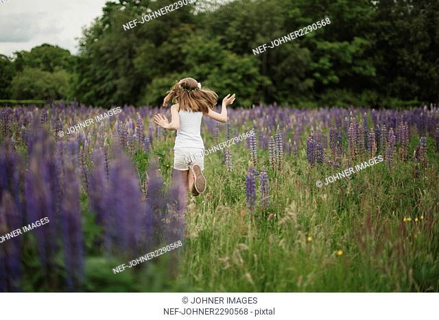 Girl running through meadow