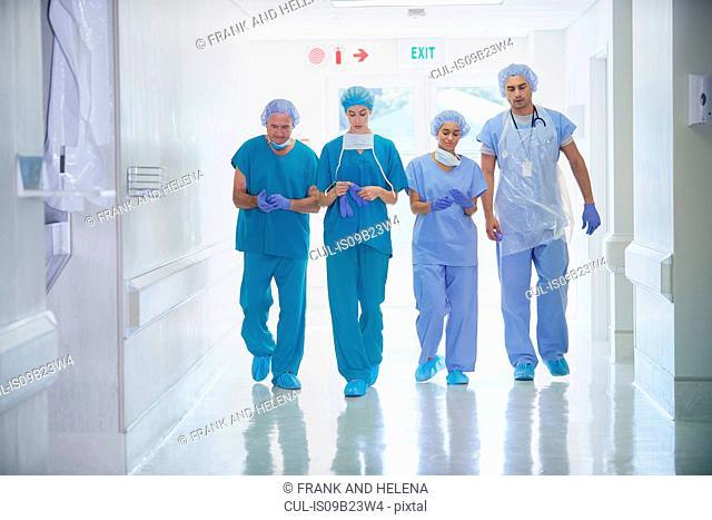 Four medical staff wearing scrubs walking in hospital corridor